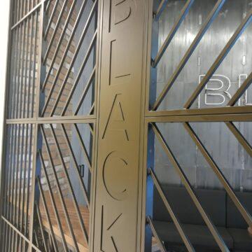 Входная металлическая решётка в кофейне Black Appolo-2. Лого
