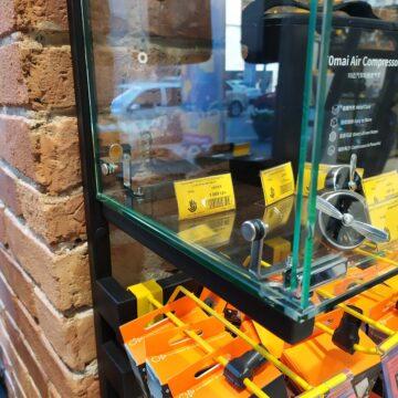 Навесные крючки под стеклянным кубом настенной витрины в магазине электроники и гаджетов